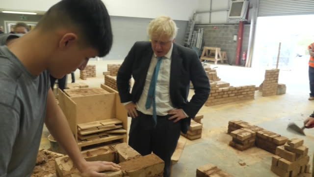 prime minister boris johnson giving a social distanced elbow bump greeting to apprentice builders - skill stock videos & royalty-free footage