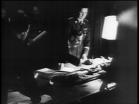 stockvideo's en b-roll-footage met prime minister chamberlain leaning over desk signing document / munich pact - 1938