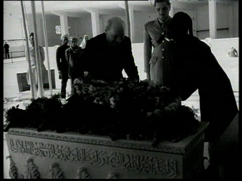 vídeos y material grabado en eventos de stock de prime minister clement attlee flanked by soldier lays wreath on tomb during tour of pakistan jan 53 - primer ministro británico