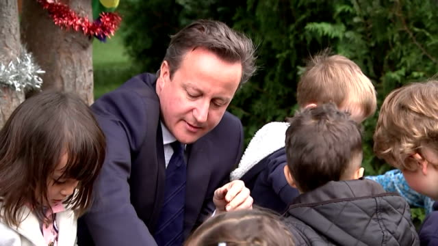prime minister david cameron and priti patel minister of state for employment planting in garden with children at teddington nursery the government... - priti patel stock-videos und b-roll-filmmaterial