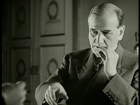 stockvideo's en b-roll-footage met prime minister edouard daladier licking tobacco roll seal taking match lighting tobacco roll puffing smoke ws cottage house workers ms row of french... - 1938