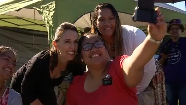 prime minister jacinda ardern posing for selfie photographs with members of the public at 2018 waitangi day festival - ニュージーランド べイ・オブ・アイランズ点の映像素材/bロール