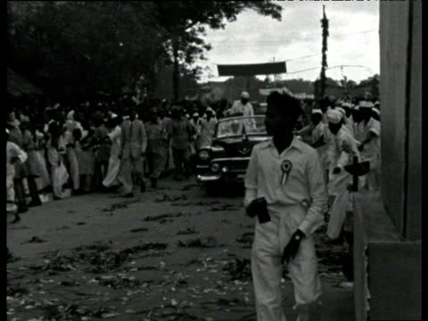 prime minister pandit jawaharlal nehru stands in open top car moving slowly down road lined with his supporters pondicherry; jan 55 - prime minister bildbanksvideor och videomaterial från bakom kulisserna