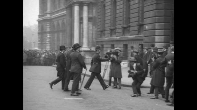 vs prime minister ramsay macdonald leaves 10 downing street and quickly walks past cameras / a crowd at the gates to buckingham palace waits to hear... - 1924 stock videos and b-roll footage