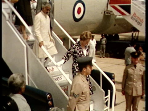 Prime Minister Thatcher visit New Delhi MS Mrs Thatcher down plane steps and shakes hands with Mrs Gandhi ZOOM IN TMS Inspects Guard of Honour MS...
