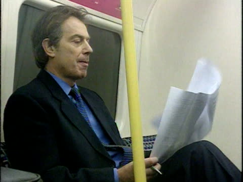 vídeos de stock, filmes e b-roll de prime minister tony blair looks at paperwork while riding on tube train; 1999 - primeiro ministro