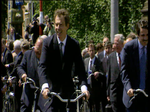 prime minister tony blair waves while riding bike though streets of amsterdam; jun 97 - political party stock videos & royalty-free footage