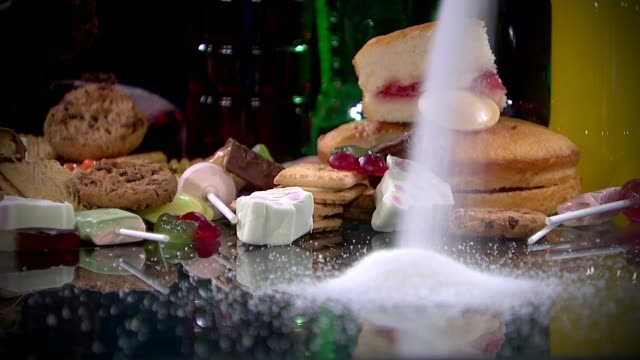prime minister under pressure on sugar tax; t22101519 / cakes, biscuits and sweets on table as sugar poured in front - sugar stock videos & royalty-free footage
