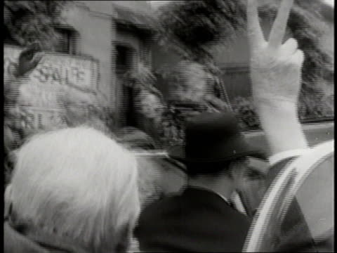 stockvideo's en b-roll-footage met prime minister winston churchill gives the victory sign while riding in a convertible through a crowd. - 1955