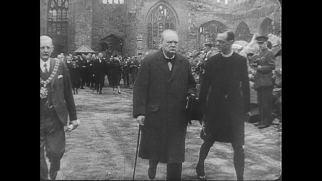 prime minister winston churchill walks along with a vicar through the rubble of a coventry cathedral , during the blitz / people's hands making the... - コベントリー点の映像素材/bロール