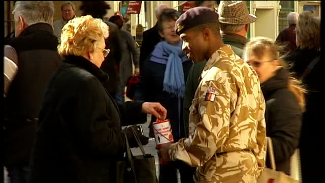 prime minster urges military to remain in uniform amidst attack fears stamford ext black soldier with collection tin in shopping street - military uniform stock videos and b-roll footage