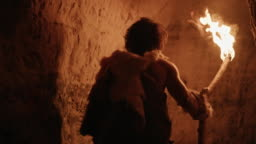 Primeval Caveman Wearing Animal Skin Exploring Cave At Night Holding Torch with Fire Looking at Drawings on the Walls at Night. Neanderthal Searching Safe Place to Spend the Night. Back View Following