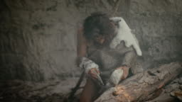 Primeval Caveman Wearing Animal Skin Holds Sharp Stone and Makes First Primitive Tool for Hunting Animal Prey, or to Handle Hides. Neanderthal Using Handax. Dawn of Human Civilization