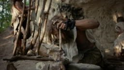 Primeval Caveman Wearing Animal Skin Trying to make a Fire with Bow Drill Method. Neanderthal Kindle First Man-Made fire in the Human Civilization History. Making Fire for Cooking. Slow Motion