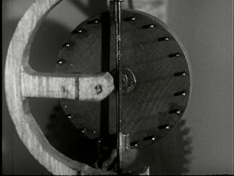 1943 film montage ms primitive clockwork mechanism/ cu rotating pegged disc driving gears/ ms clock/ audio - clockworks stock videos & royalty-free footage