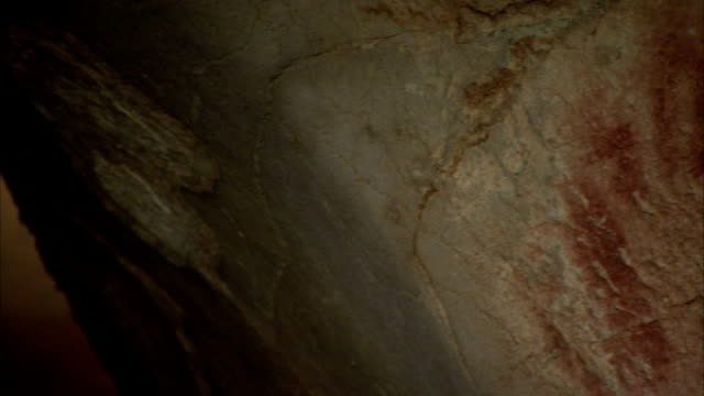 primitive painting and images of human hands cover the wall of a cave. available in hd - cave painting stock videos & royalty-free footage