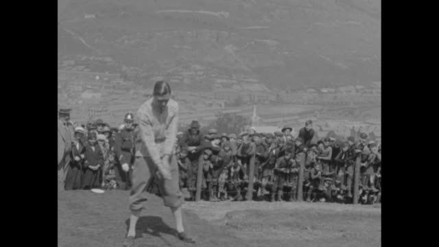 prince albert duke of york takes a practice swing and then tees off during a golf match spectators look on police officer stands by / frank hodges... - british royalty stock videos & royalty-free footage