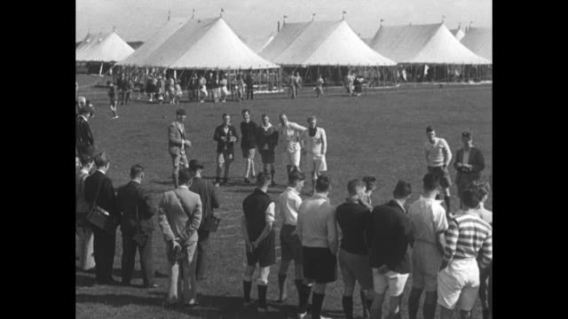 king george vi in shorts and jacket walks through crowd of boys clapping tents in background / vs george watches ball toss / ms george walks and... - 1930 stock-videos und b-roll-filmmaterial