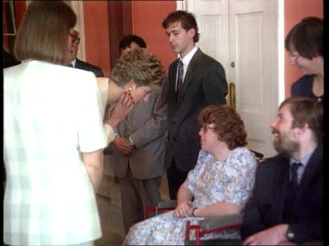 Prince and Princess of Wales' marriage Location Unknown Diana talking to woman in wheelchair CMS SIDE Cameraman filming BV Diana chatting to man in...