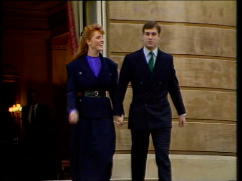 Prince Andrew and Sarah Ferguson walk out of Buckingham Palace hand in hand smiling for press after announcement of their engagement 19 Mar 86