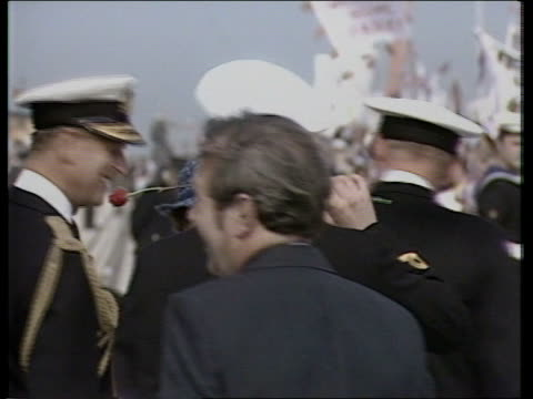 prince andrew's girlfriend tx 17982 spithead ms prince andrew in naval uniform places rose in mouth and prince philip turns to laugh tms queen down... - ヨーク公 アンドルー王子点の映像素材/bロール