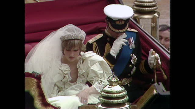 prince charles and bridesmaids assist princess diana into the coach outside st paul's cathedral on the day of their wedding; 1981. - symbol stock videos & royalty-free footage