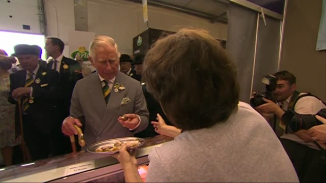 vídeos de stock e filmes b-roll de prince charles and camilla attend great yorkshire show; int prince charles talking woman at stall and tasting pie / people selling produce - pie humano