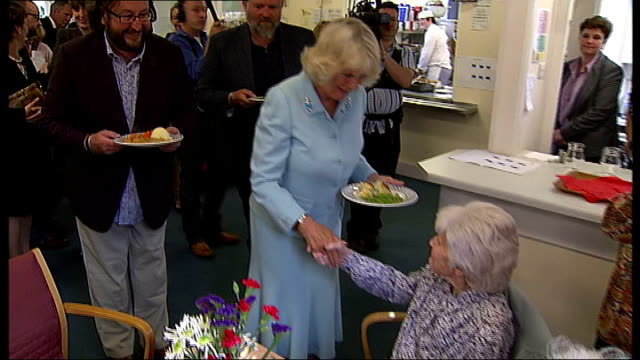 vídeos de stock, filmes e b-roll de prince charles and duchess of cornwall visit denbies wine estate; camilla along from kitchen with fish pie and serving to elderly woman ends - pie humano