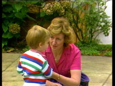 Prince Charles and Princess Diana escort Prince William to greet nursery school head mistress on his first day whereupon he waves to press and...
