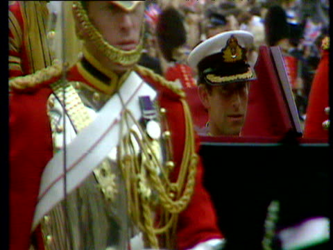 Prince Charles and Princess Diana in horse drawn carriage flanked by guardsmen wave to crowds after their Royal Wedding St Paul's Cathedral 29 Jul...