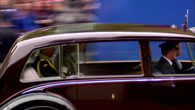 Prince Charles and the Duchess of Cornwall wave to the crowds from a Royal limousine as they travel to Westminster Abbey for the wedding of Prince...