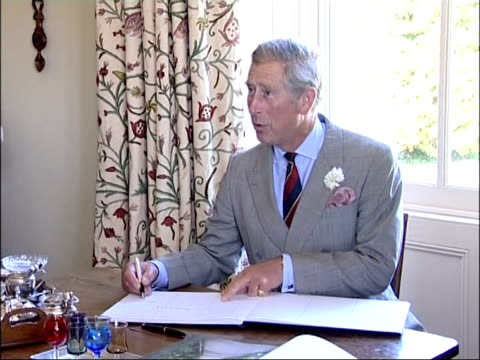 prince charles annual summer tour of wales charles signing visitors' book laughing as gets date wrong signing copies of his book 'organic gardens' - book signing stock videos & royalty-free footage