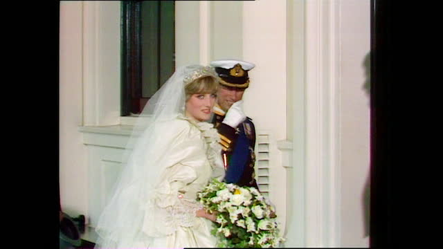 prince charles assists princess diana off the coach as they arrive and enter buckingham palace on the day of their wedding; 1981. - bouquet stock videos & royalty-free footage