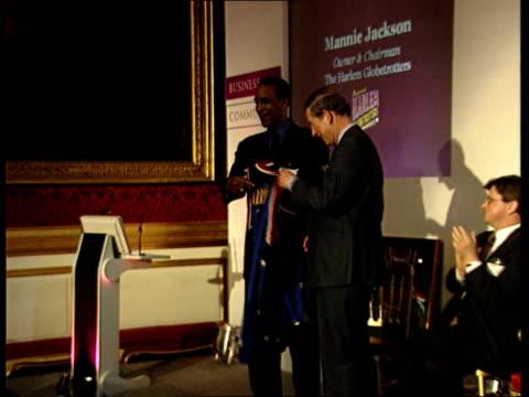 prince charles given harlem globetrotter basketball shirts; en: bong - prince charles receiving basketball shirts - ハーレムグローブトロッターズ点の映像素材/bロール