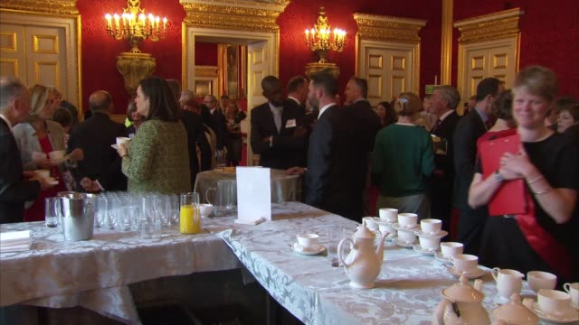 Prince Charles hosts Prince's Trust reception at St James's Palace Charles chatting to people as holding tea cup / people in reception / sign warning...
