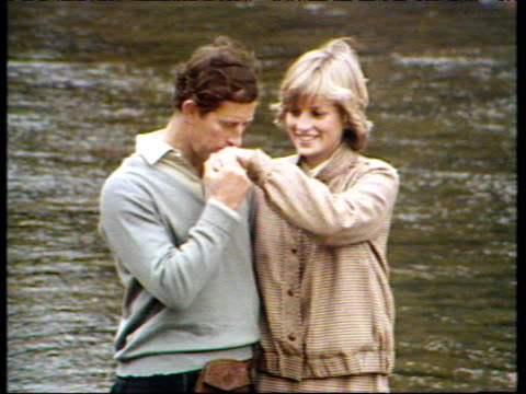 vídeos de stock, filmes e b-roll de prince charles kisses princess diana's hand whilst posing for photographers beside river dee during honeymoon balmoral 19 aug 81 - lua de mel