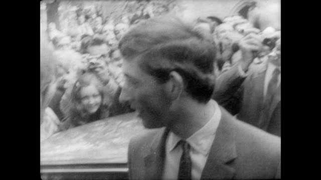 Prince Charles of England gets out of a car surrounded by press / Lord Butler Master of Trinity college greets the royal freshman / Charles looks...