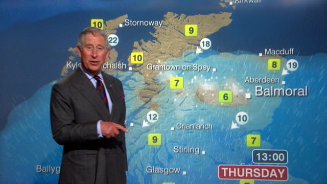 vídeos de stock e filmes b-roll de prince charles presents television weather forecast; scotland: glasgow: bbc scotland: ext / rain prince charles and camilla duchess of cornwall... - realeza