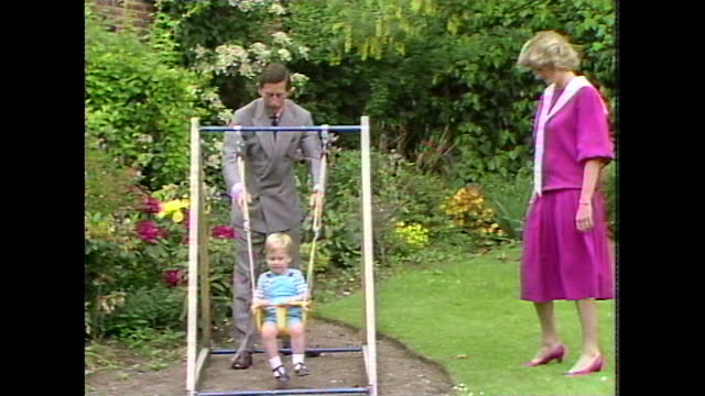 prince charles pushes two-year-old prince william on a small swing as princess diana watches during a photocall at kensington palace gardens. - toddler stock videos & royalty-free footage