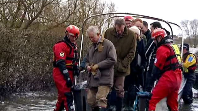 stockvideo's en b-roll-footage met prince charles tours flooded parts of somerset; charles shakes hands with emergency service personnel as gets off police boat charles' wellingtons... - rubberlaars