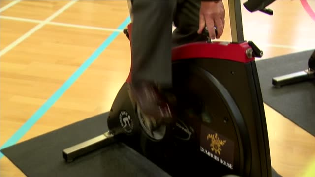 prince charles visit to dumfries house; charles along in spin class / charles using exercise bike in spin class / charles along in spin class - インドアサイクリング点の映像素材/bロール