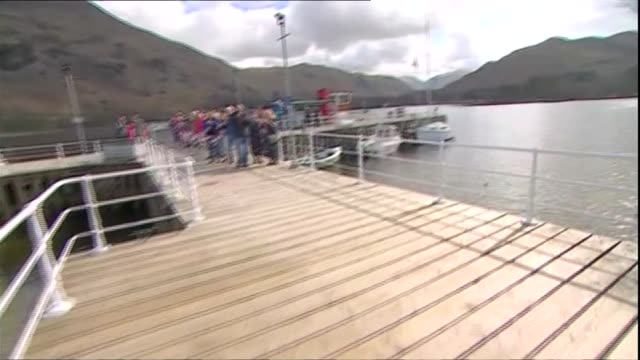 cumbria ullswater ext 'lady wakefield' boat moored on jetty / people gathered around picnic benches / people waving union jack flags / convoy... - convoy stock videos & royalty-free footage
