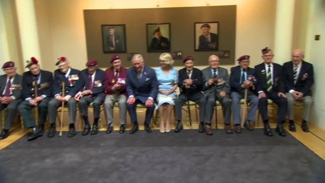 wwii prince charles visits dday veterans portrait exhibition prince charles and camiolla duchess of cornwall sit for group photograph with dday... - アロマンシェス点の映像素材/bロール