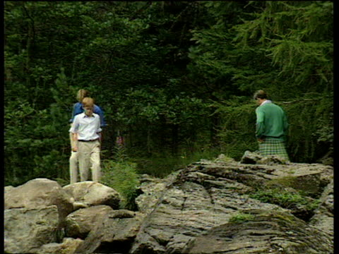 Prince Charles wearing kilt with Harry and William walking on rocks by river and forest zoom out to them walking near small waterfall 12 Aug 97