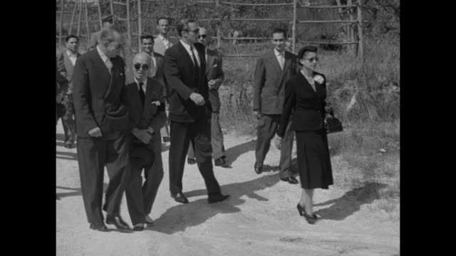 Prince Constantine Queen Frederica walking in sand on Naples beach followed by King Paul with Queen and King in sunglasses King talks laughs with man...