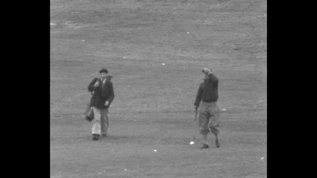 prince edward and prince gustaf adolf briskly walking up hill past camera, closely followed by caddie / edward taking club out of golf bag, taking... - 皇族・王族点の映像素材/bロール