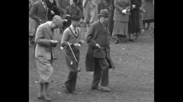 prince edward and prince gustaf adolf of sweden walking with golf clubs resting on folded forearms handles under armpits entourage in tow / vs... - armpit stock videos and b-roll footage