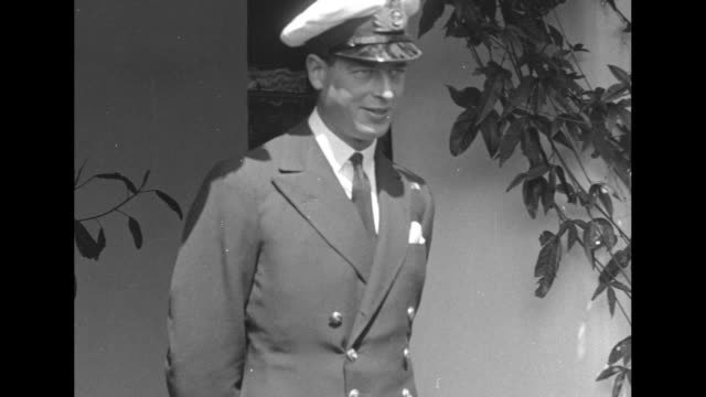 MS Prince George Duke of Kent stands outdoors wearing Royal Navy uniform / an honor guard possibly of police stands behind George as he walks then...