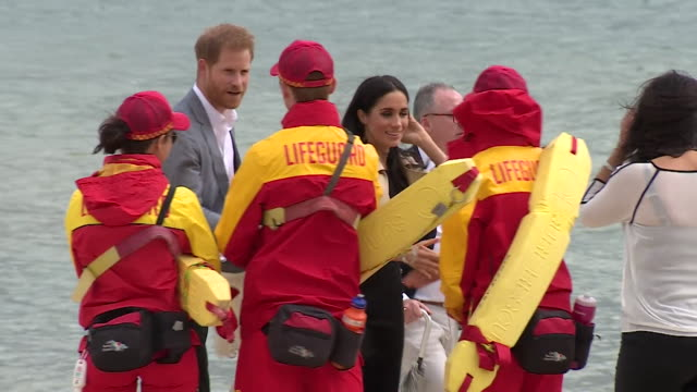 Prince Harry and Meghan Duchess of Sussex greeting lifeguards and fans on a visit to Melbourne Australia