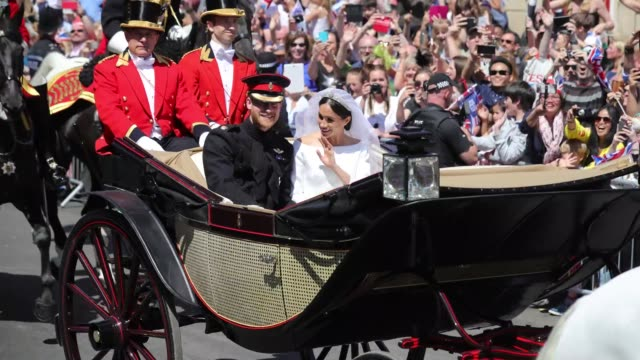 prince harry and meghan duchess of sussex ride on an open top carriage on the procession route through windsor after their marriage on may 19 2018 in... - königliche hochzeit stock-videos und b-roll-filmmaterial